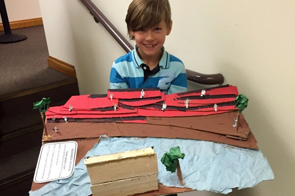 A student holds his group's prototype for an outdoor learning center and movie theater