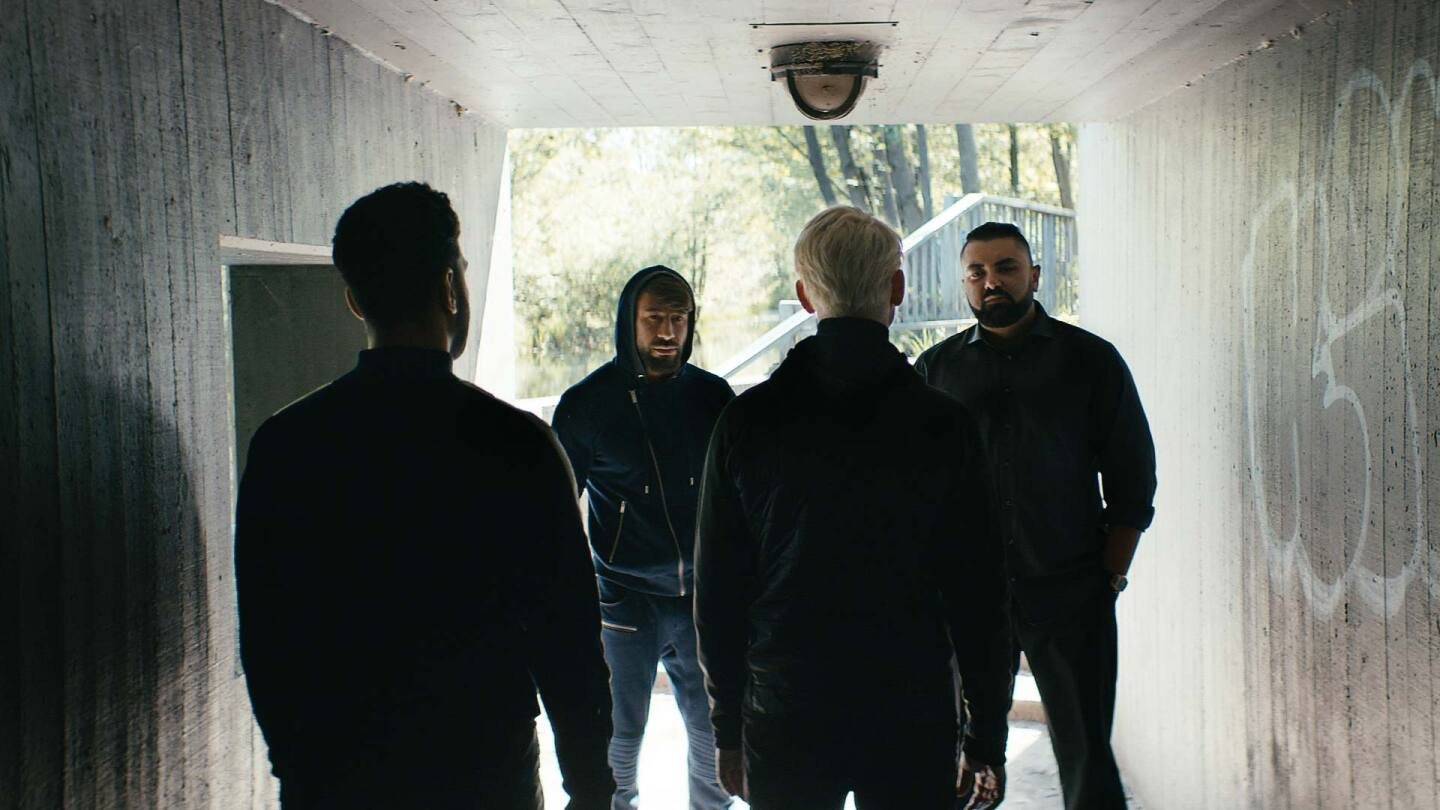 """Nicky surrounded by men in a tunnel. 