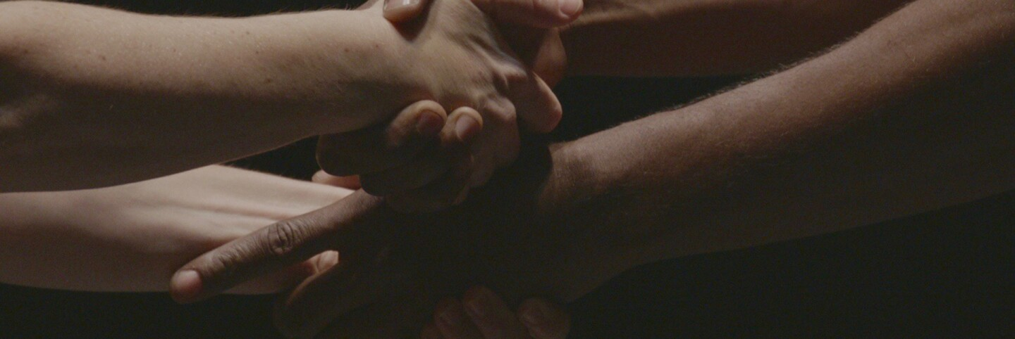 """Clasped hands from """"D-Man in the Waters"""" performance. 