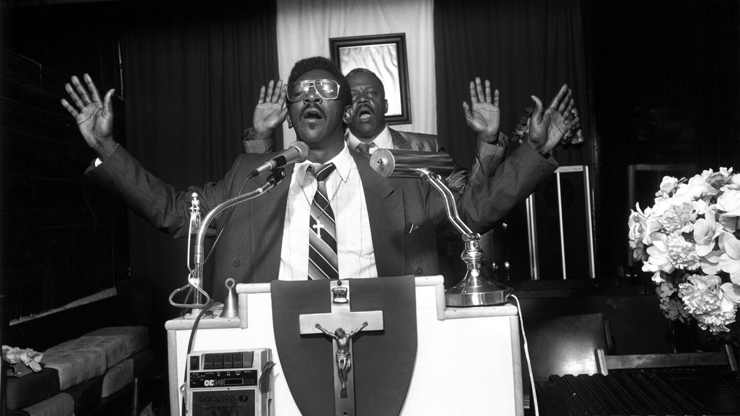 Two men, preaching, arms outstretched with Jesus Christ on a cross plaque hanging on the podium.