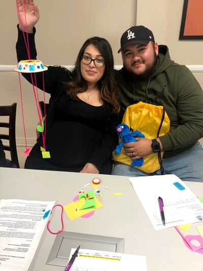 A couple hold their completed shape mobile.