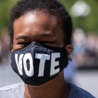 """African American protester wearing a mask that says, """"Vote"""" in Washington Square Park expressing the sentiment that voting in Nov. 2020 will be a way to help affect change in policies to end racial injustice. June 19, 2020. 