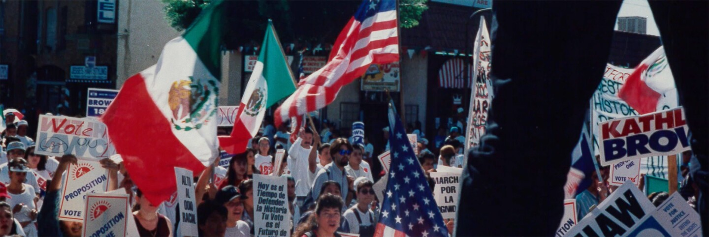"Rally against Prop 187 with American and Mexican flags waving | Still from ""187"""