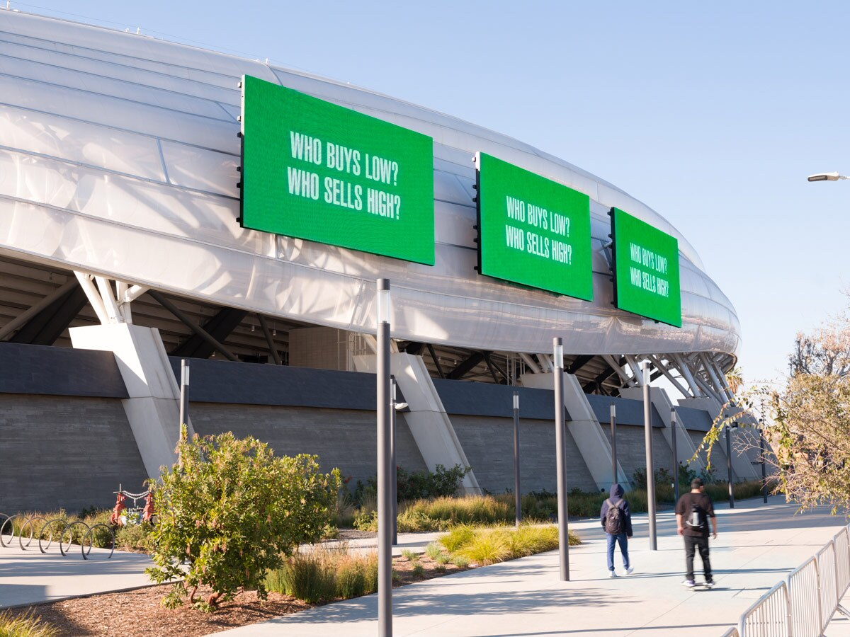 """A digital billboard at the Banc of California Stadium reads """"Who buys low?"""" Who sells high?""""as part of Barbara Kruger's """"Untitled (Questions)"""" 