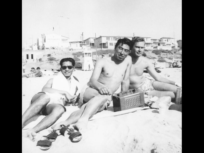 Black and white photo of three men sitting together on a beach