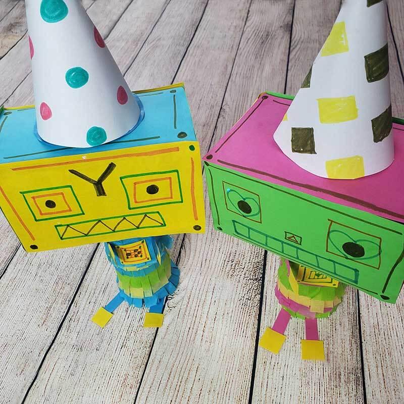 Dos robots coloridos hechos de papel de construcción.