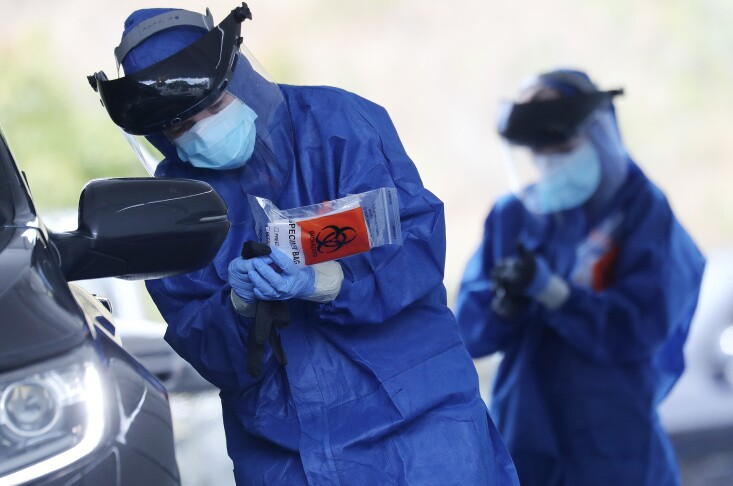A volunteer in personal protective equipment (PPE) holds a specimen bag while conducting drive-through coronavirus testing at Malibu City Hall on April 8, 2020 in Malibu, California.   Mario Tama/Getty Images