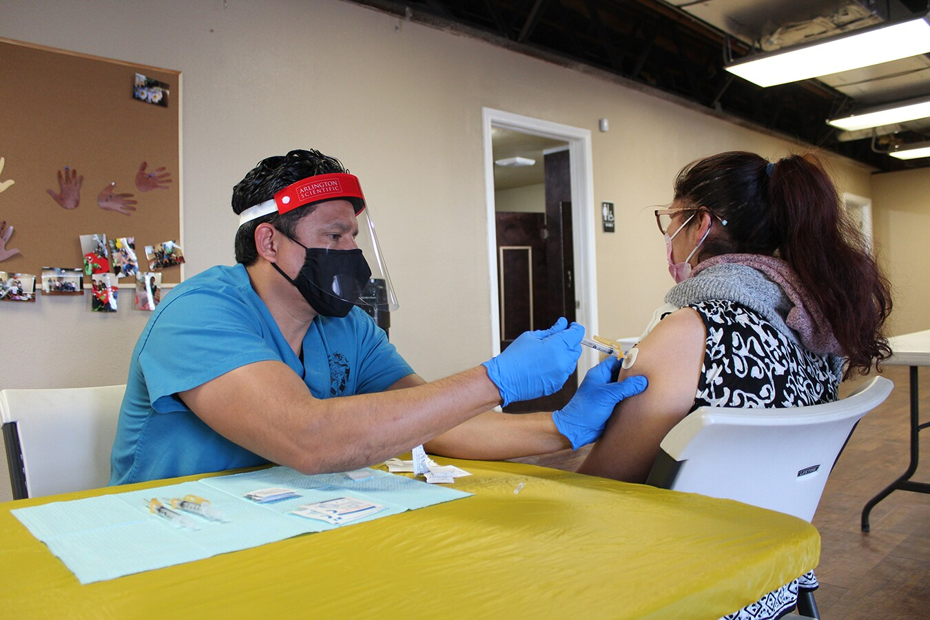 A woman receives her COVID vaccine by a yellow table. The shot is being administered by a man in teal blue scrubs.