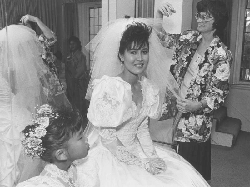 Bride to be Chan Yong Candice Park sits in her wedding dress with voluminous sleeves as wedding coordinator, Lori Jones, adjusts her veil in this black and white photo