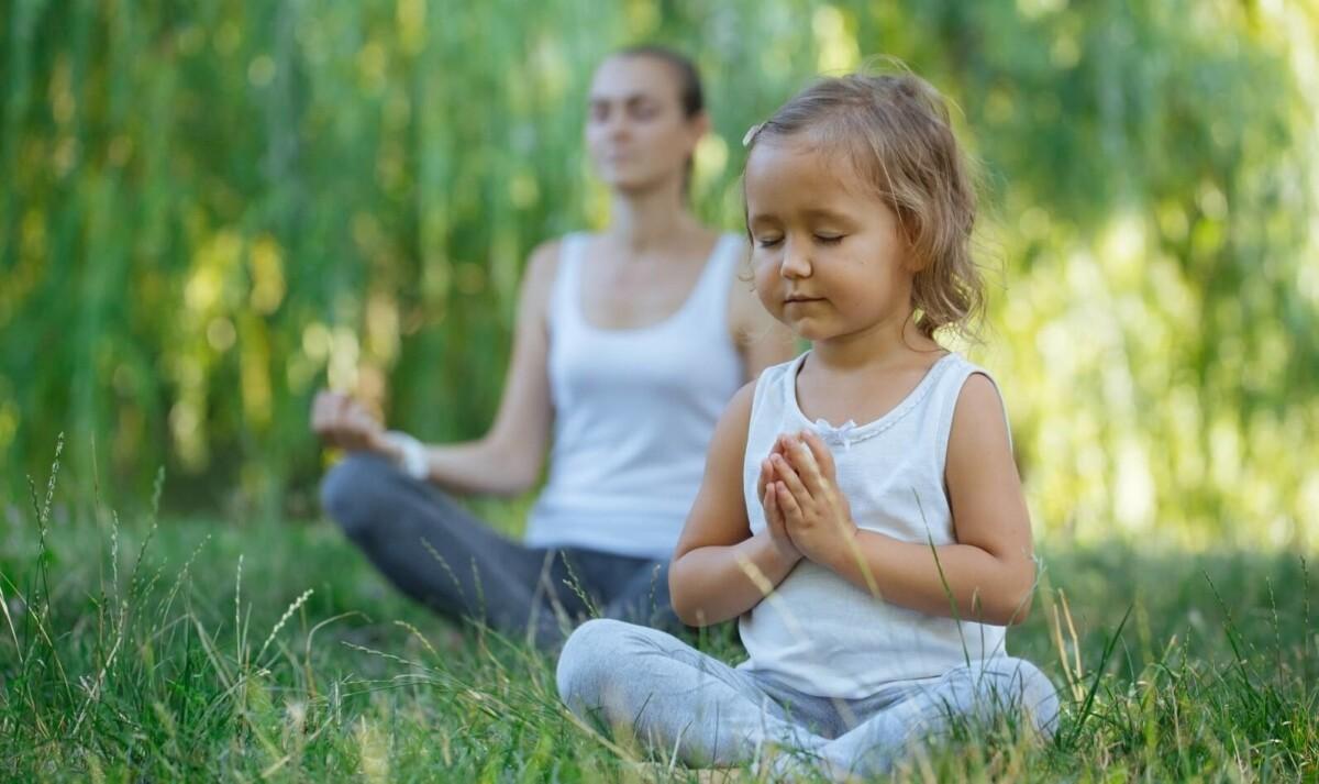 Una niña chiquita sentada sobre zacate en frente de su mamá con las piernas cruzadas y los ojos cerrados