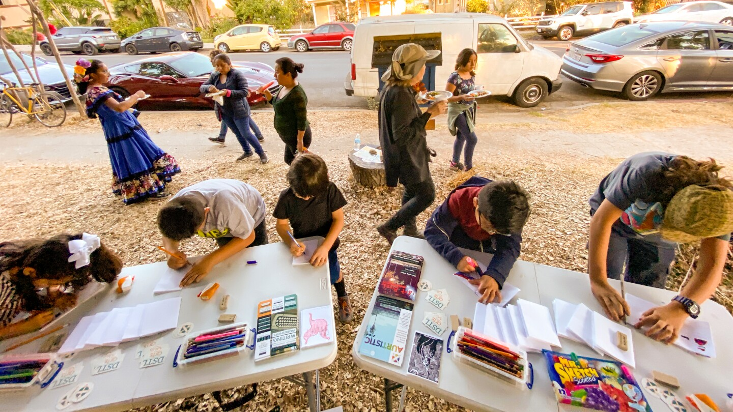 Participants make zines on outdoor tables. Behind them, people are standing around and eating food.