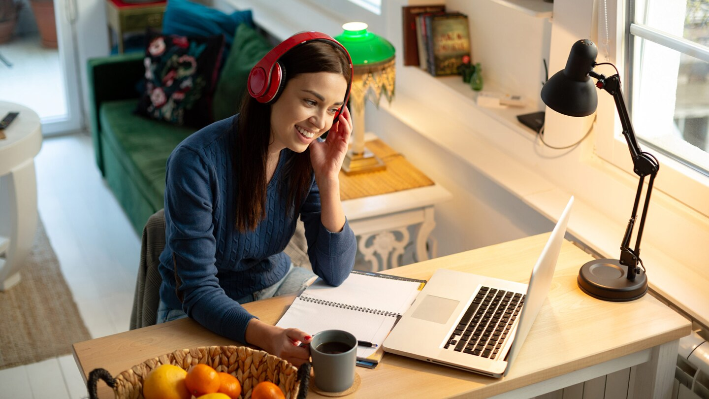 A young female teacher wearing red headphones works at a desk with a laptop on it.