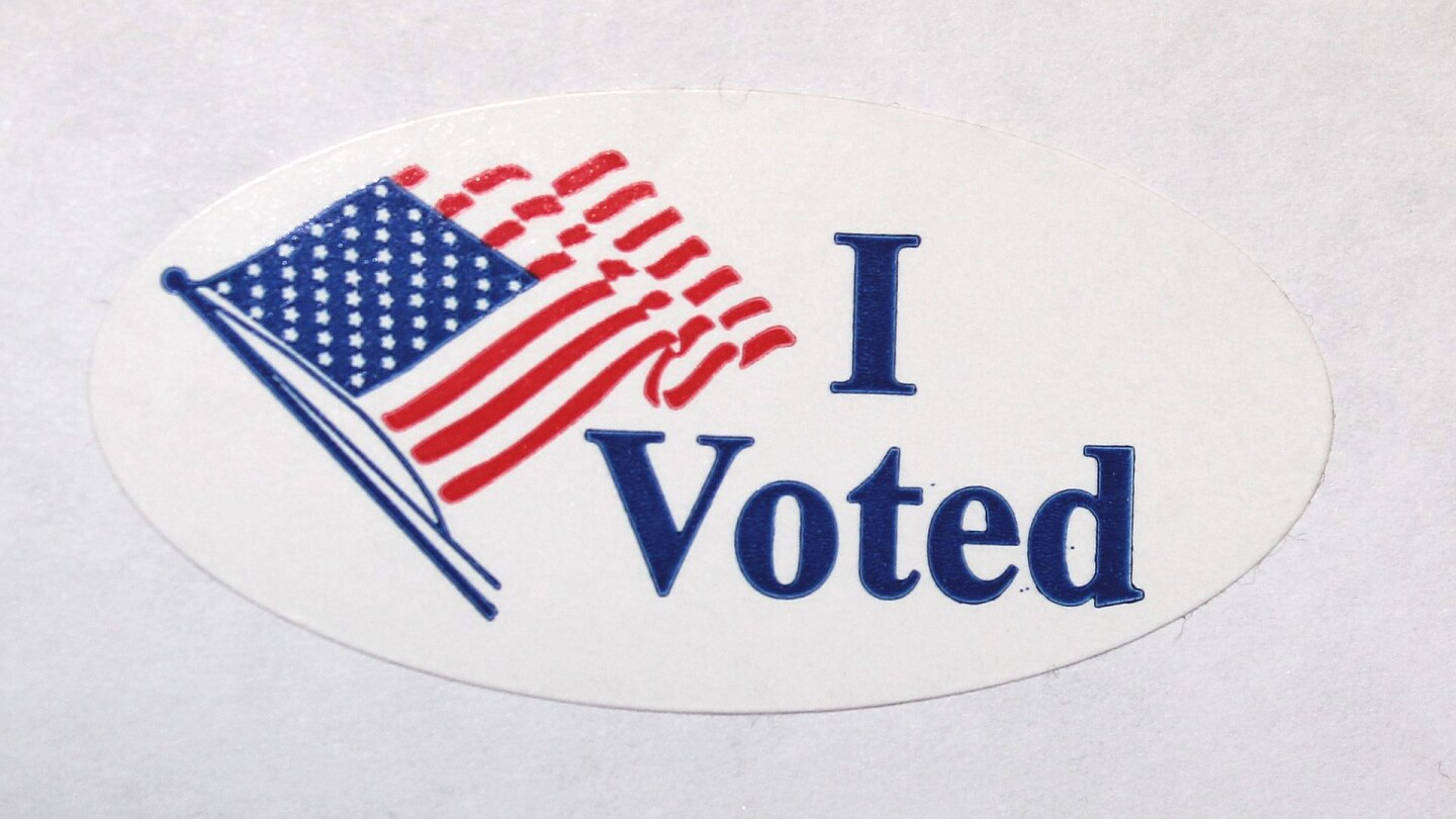 """An oval sticker with an American flag and the words """"I Voted"""""""
