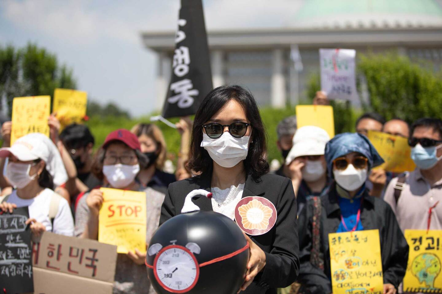 A demonstrator in Seoul, South Korea holds a time bomb symbolizing the climate crisis in June 2020. Demonstrators wear masks to protect themselves from the COVID-19 pandemic. |  Chris Jung/NurPhoto via Getty Images