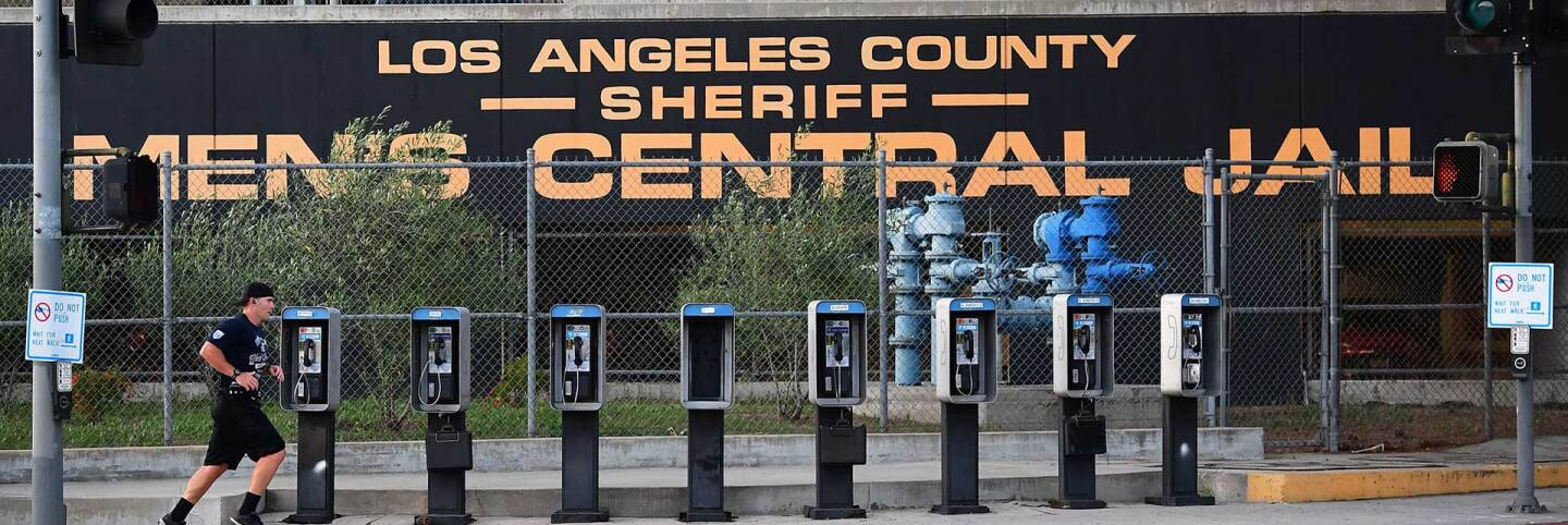 A man jogs past a row of telephone booths in front of the Los Angeles County Men's Central Jail on May 11, 2020 in Los Angeles.