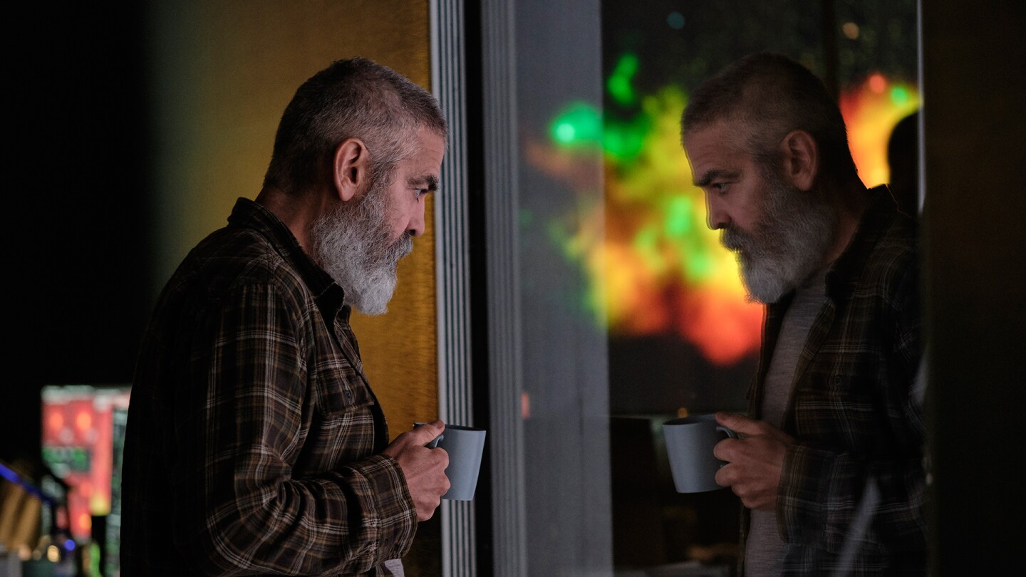 "George Clooney in ""Midnight Sky"" looks out a window with a mug in hand."