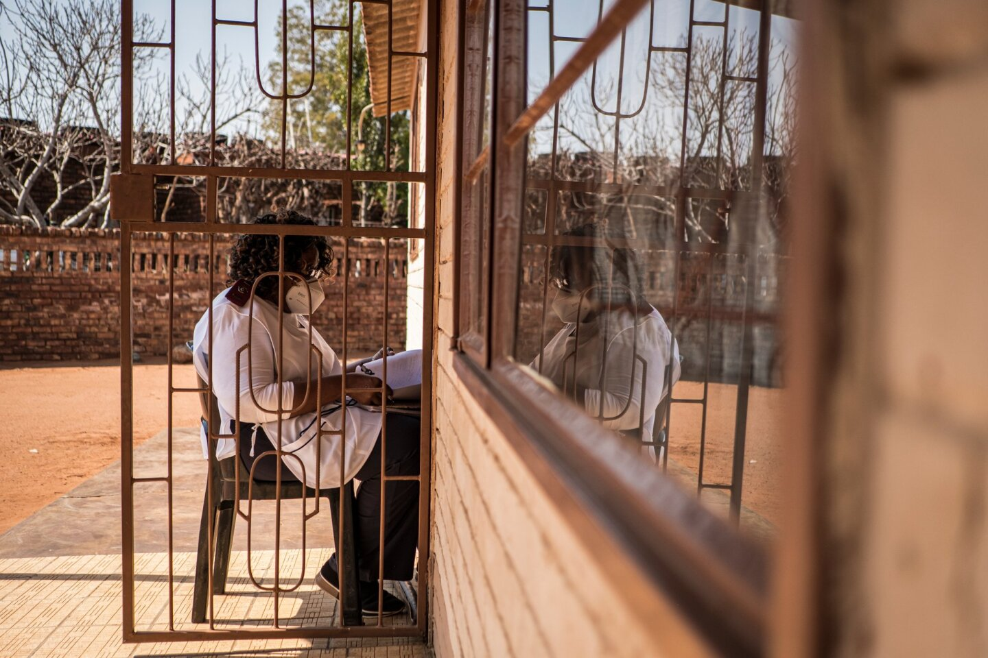 Sister Rachel Asitile (61) is pictured sitting, in accordance with social distancing measures, outside the home of a patient who tested positive for COVID-19 to do a follow up assessment. | Thomson Reuters Foundation/Gulshan Khan