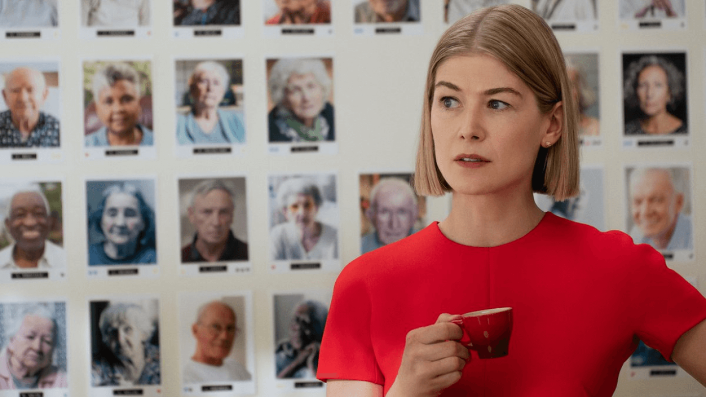 "Rosamund Pike holds a small cup in her hand as she looks to the side in a scene from ""I Care a Lot"""