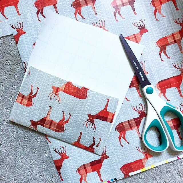 A folded piece of wrapping paper with red reindeer with some scissors next to it.