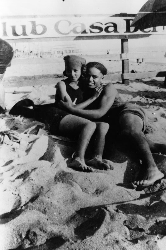 Verna and Arthur at the segregated section of the Santa Monica beach known as Ink Well, shortly before they married. They are in front of a fence with a sign for Club Casa, a private beach club. | Courtesy of the Los Angeles Public Library