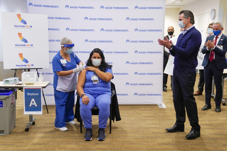 ICU Nurse Helen Cordova, center, receives the Pfizer-BioNTech Covid-19 vaccine as Gavin Newsom, governor of California, applauds at Kaiser Permanente Los Angeles Medical Center in Los Angeles, California, U.S., on Monday, Dec. 14, 2020.
