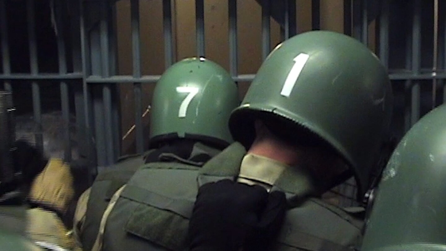 Men in Green Body Armor and Hardhats Gather in Front of Cell Bars