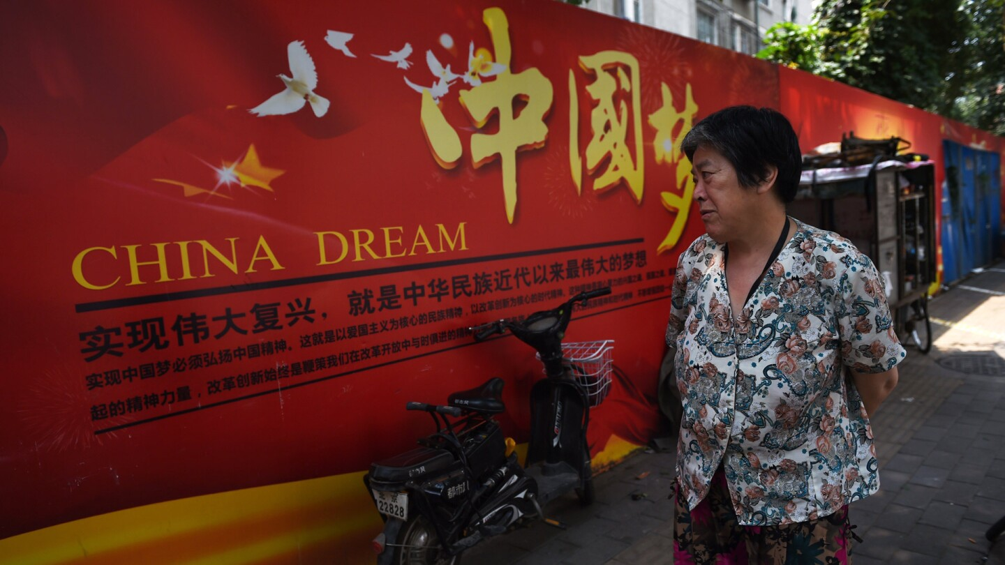 A woman looks at a banner about the 'China Dream,' Greg Baker/AFP/Getty Images