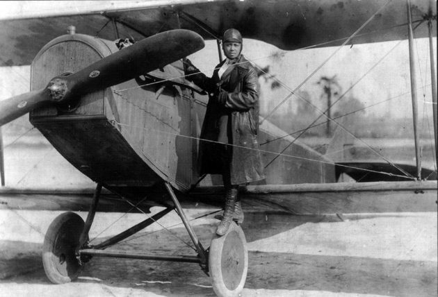 """Bessie Coleman, shown here on the wheel of a Curtiss JN-4 """"Jennie"""" in her custom-designed flying suit (circa 1924). 
