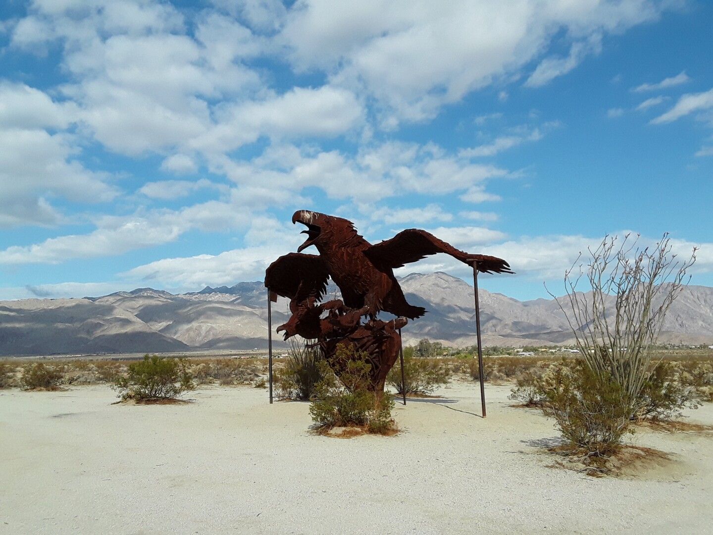 A rust-colored metal bird sculpture stands in the middle of a desert landscape. The bird's wings are outstretched and its mouth is open.
