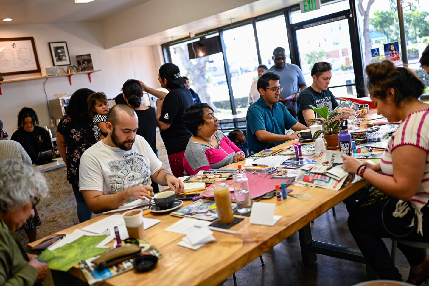 Participants make zines at a zine-making pop-up at Patria Coffee in 2018.