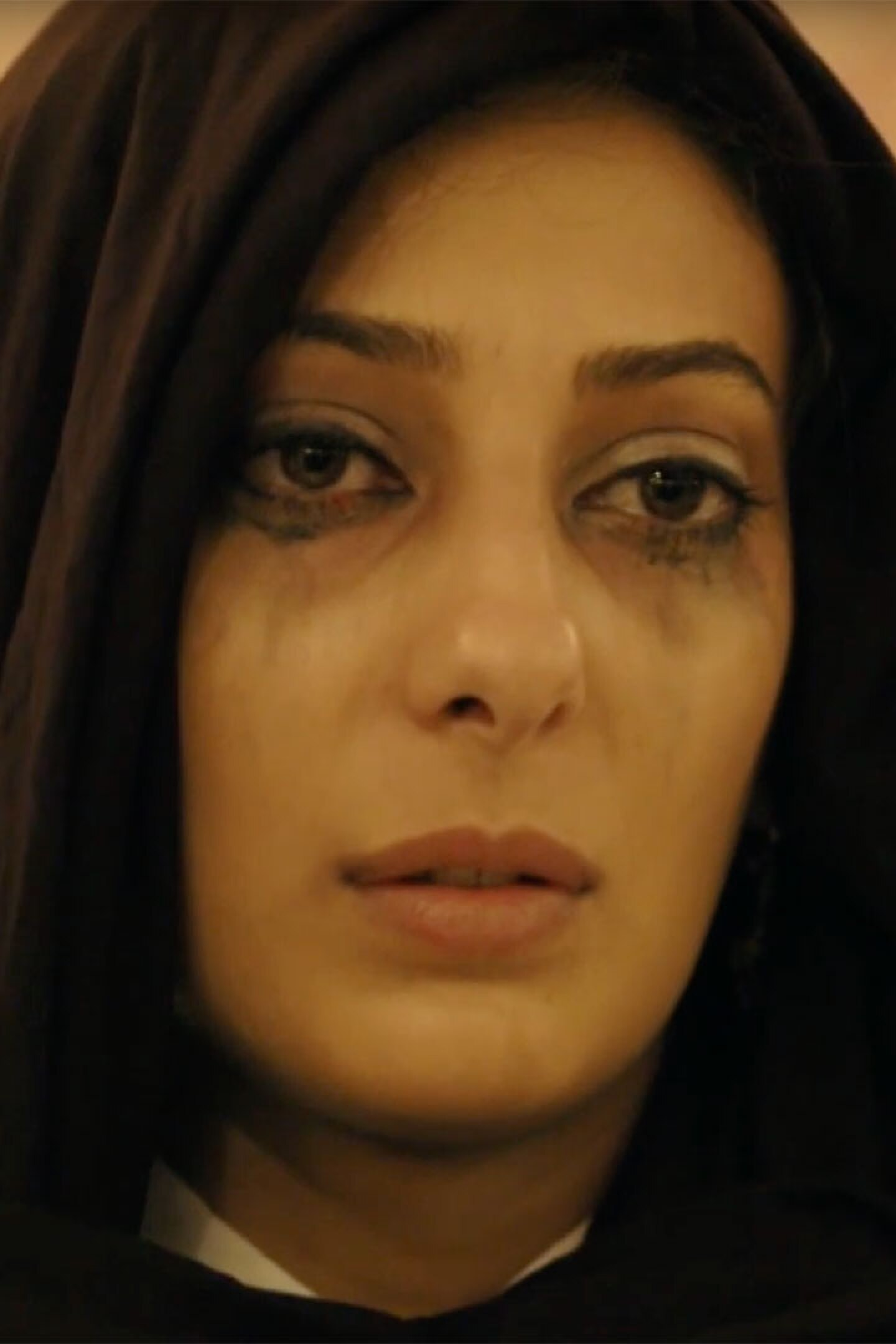 """Woman with mascara running, wearing black scarf.   Still from """"Fauda"""""""