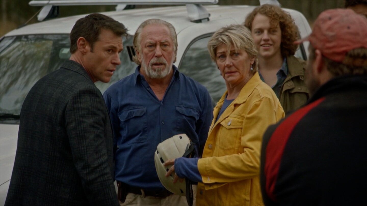 """A group of people look at a man walking toward them. 