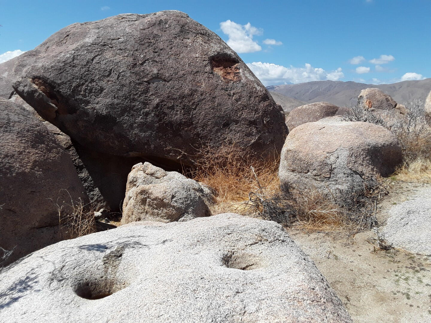 Kumeyaay Village Site at Anza-Borrego. Large boulders make up most of the landscape. At the bottom left of the photo there is a flat boulder with two medium-sized holes in it.