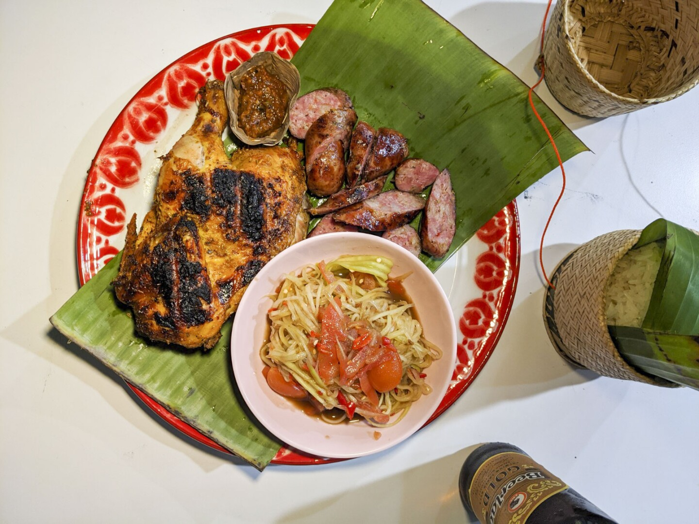 Lao sausage and chicken with papaya salad plate served with sticky rice and beer on the side. The chicken is a thigh and leg with a slight char on the skin. The Lao sausage is cut in thin slices.