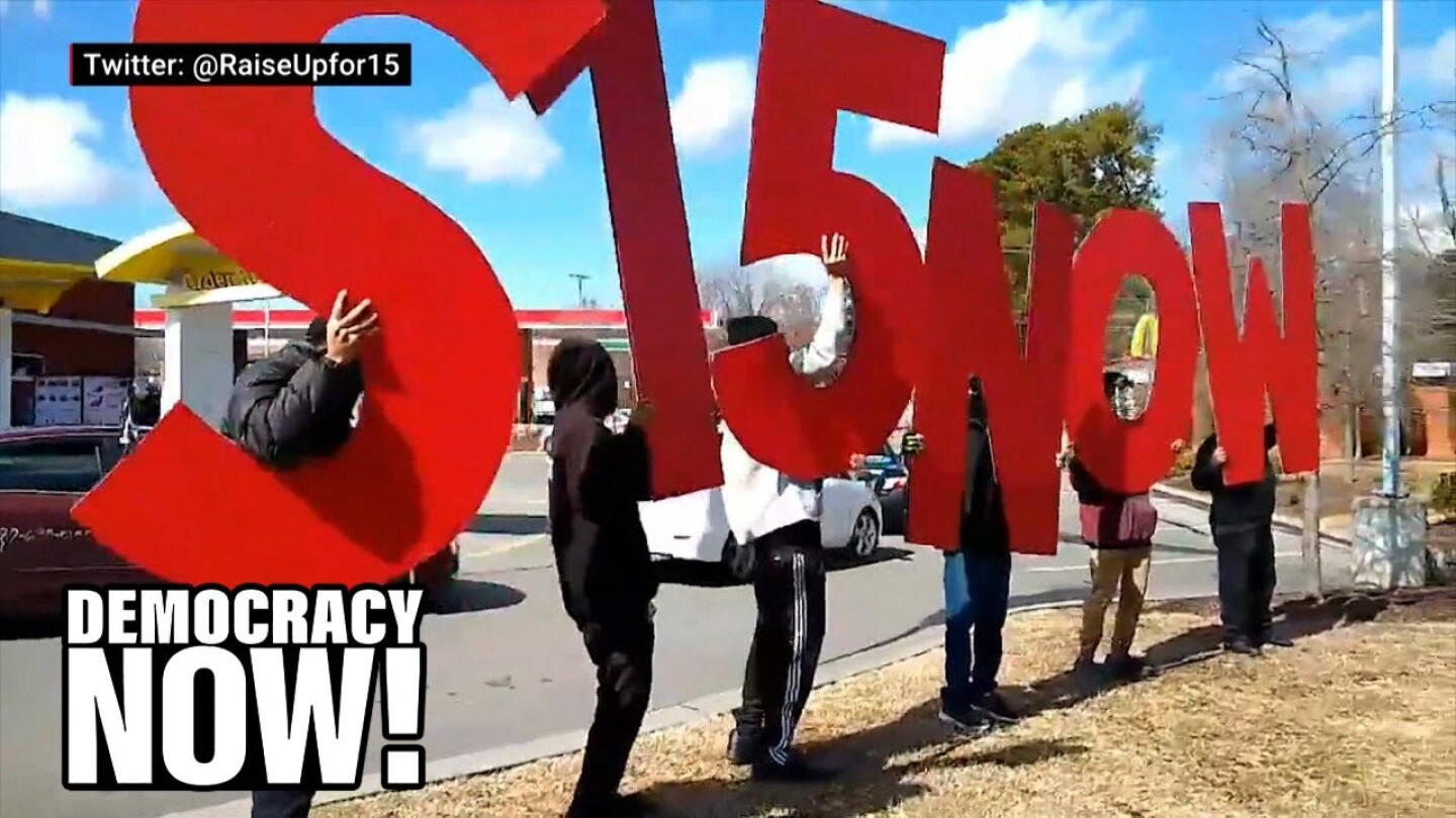 "Demonstrators hold up individual red letters that spell ""S15 NOW."""