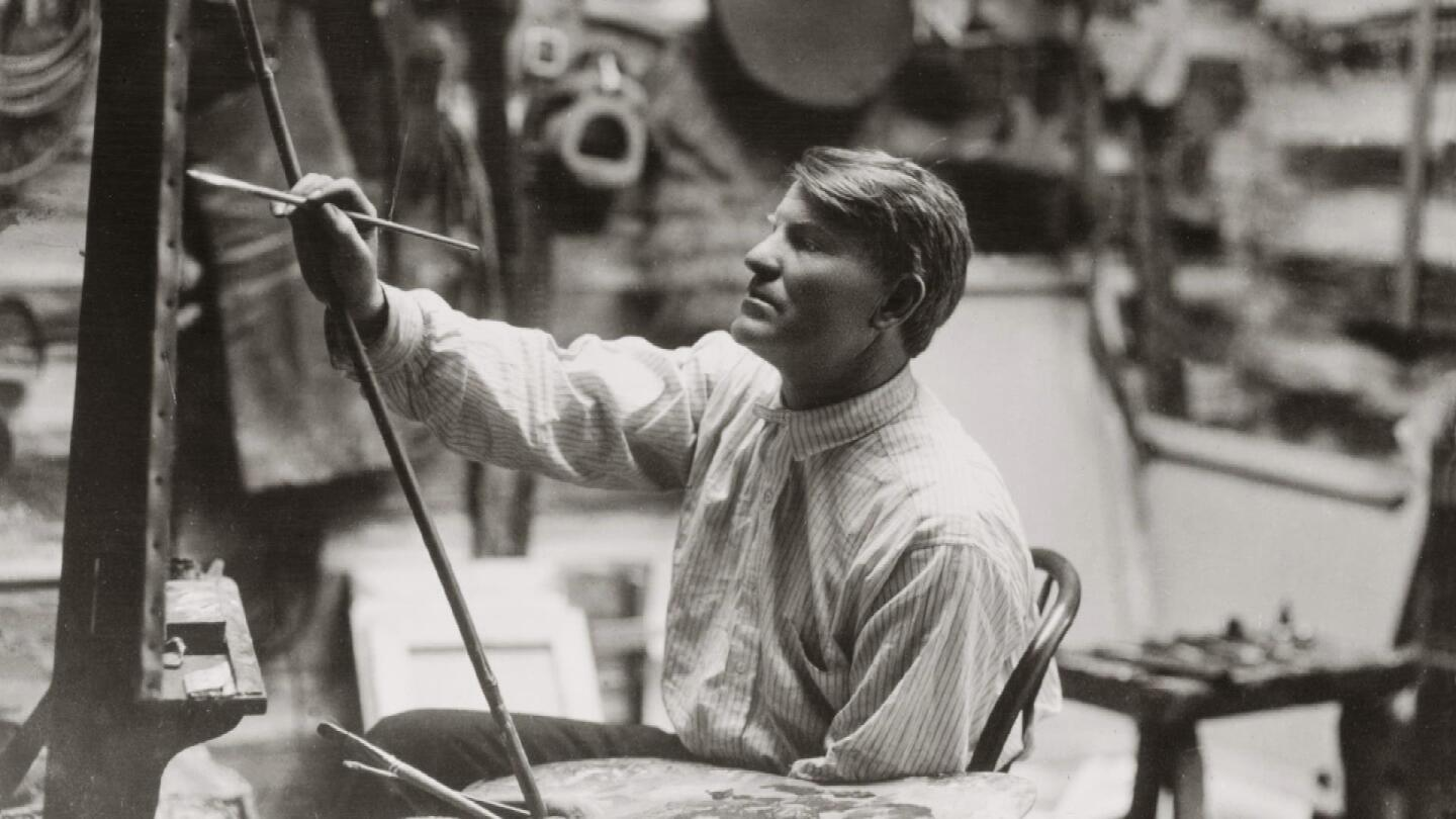 Charlie Russell sitting in a chair as he paints on a canvas.