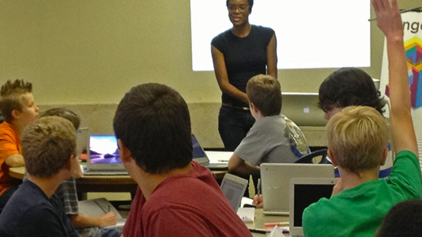 A teacher works with students learning to code.