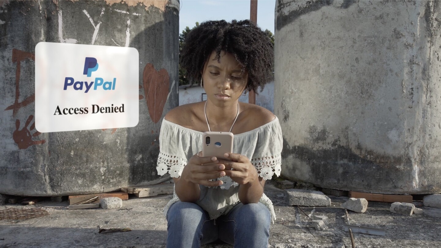 "A young woman sitting on the ground looks down at her phone, with an ""Access Denied"" pop-up next to her."