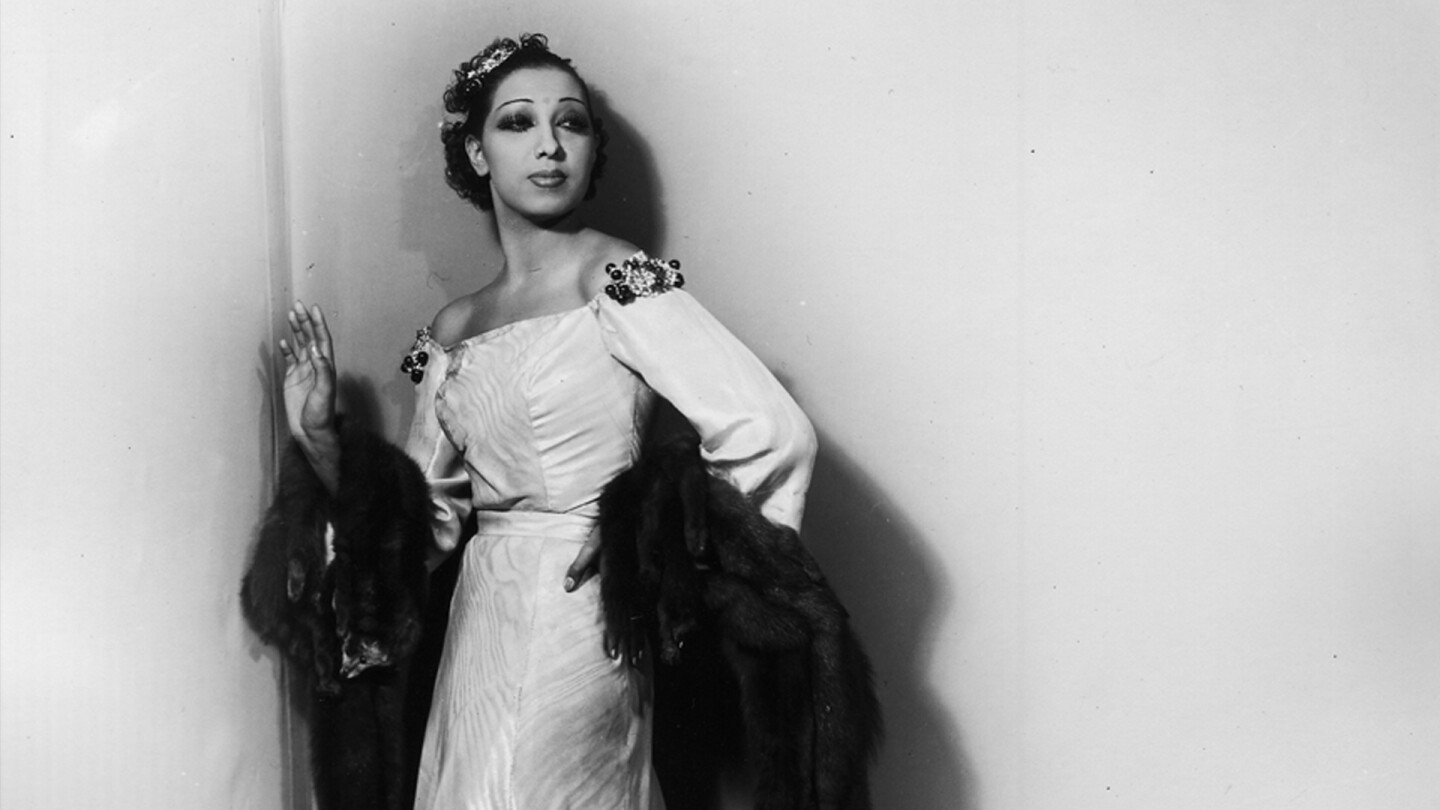 Josephine Baker poses against a wall.