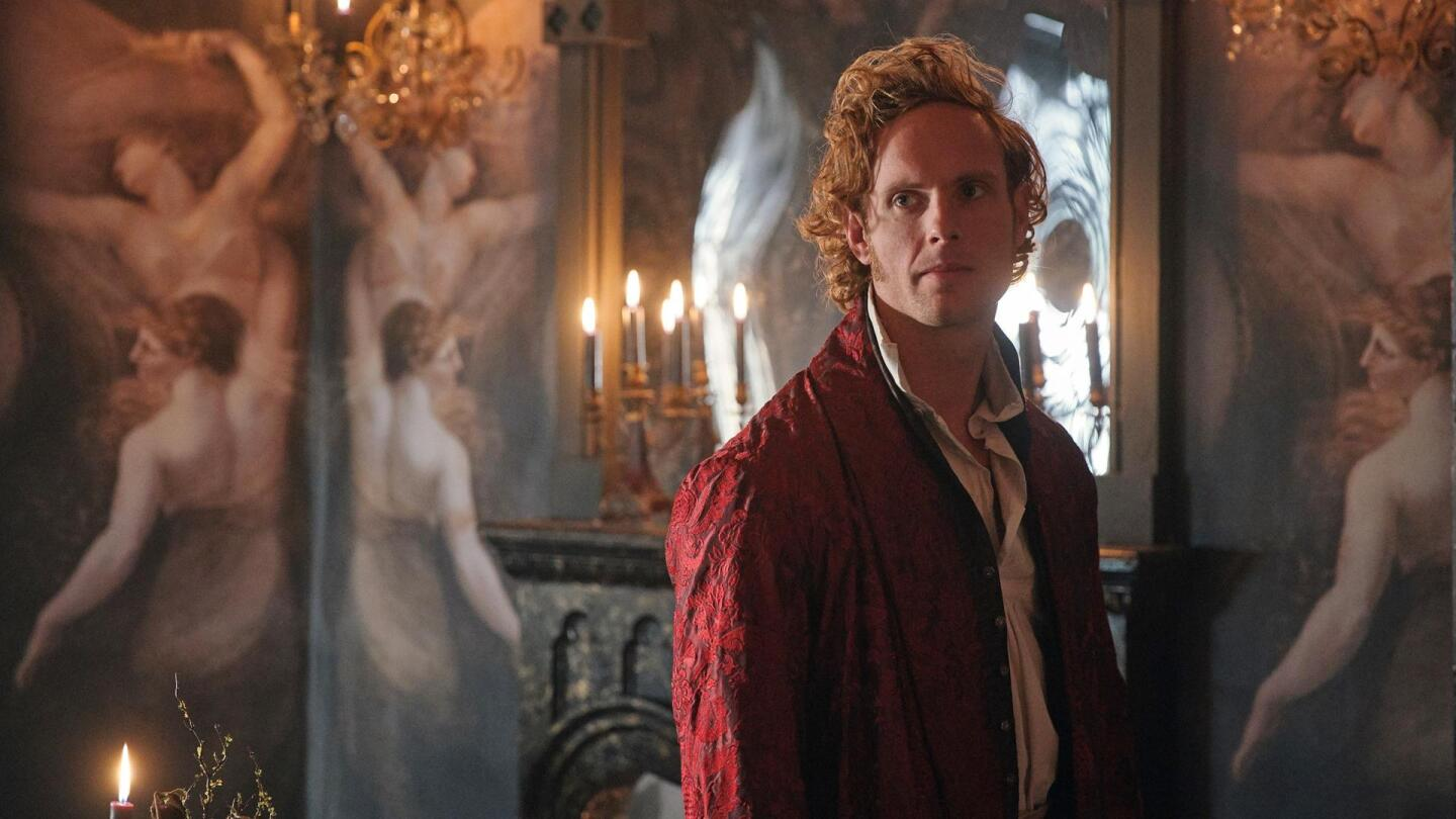 """A disheveled man looks to the side in a candlelit room. 