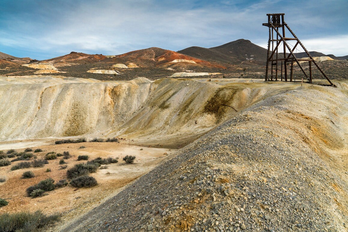 "A newly constructed headframe of a ""hobby mine"" with numerous historic Goldfield mines pictured in the distance. 