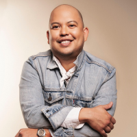 A portrait of Anthony Ocampo. He's wearing a light-wash denim jacket with his arms folded across his chest.