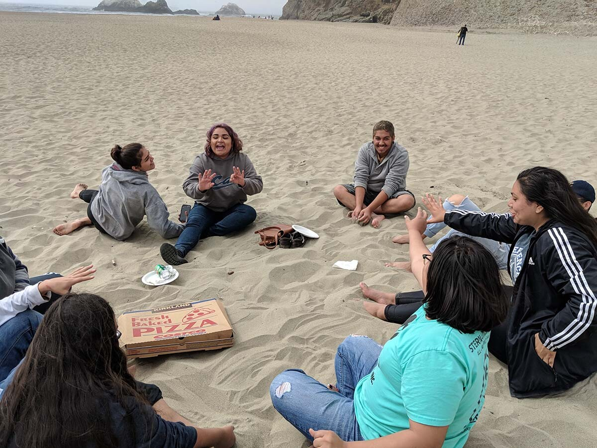 Californians for Justice youths eating pizza at the beach. It is a rare experience for many since most are juggling multiple responsibilities created by social and economic systems. | Californians for Justice