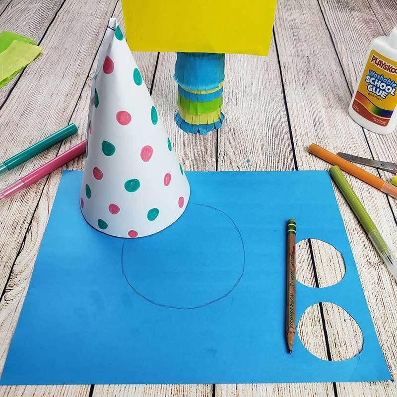 Una hoja de papel colorida con forma de cono se coloca encima de una cartulina azul, rodeada de otros materiales de manualidades.