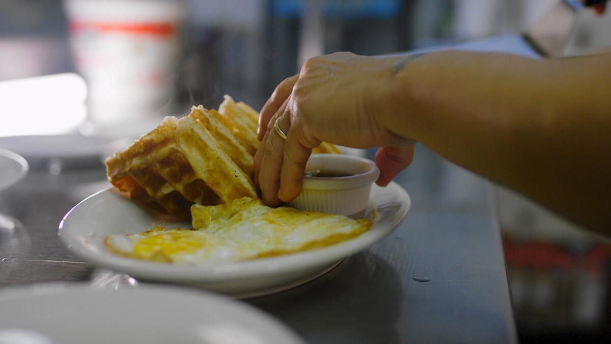 "A breakfast with waffles from Watts Coffee House. | Still from ""Broken Bread"" Watts"