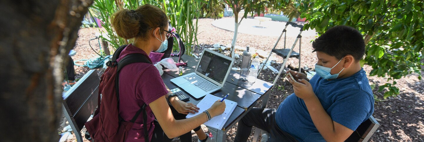 East College Prep High School senior Jocelyn Hernandez follows a remote Advanced Placement (AP) Calculus class as her cousin plays with his phone while sitting in a community garden near her home, August 14, 2020 Boyle Heights. | ROBYN BECK/AFP via Getty
