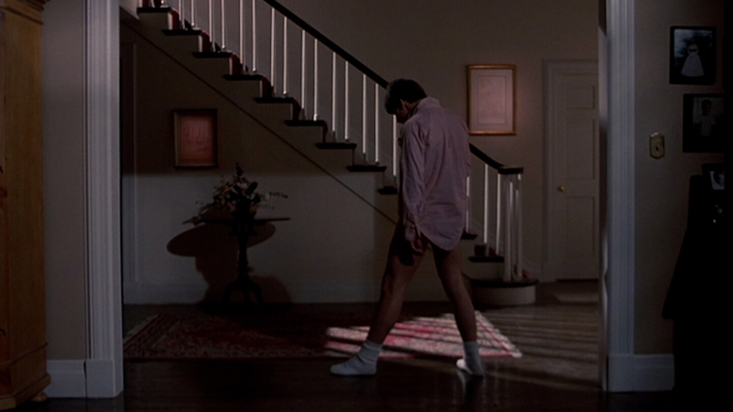 Person wearing a pink dress shirt and socks slides through a hallway.