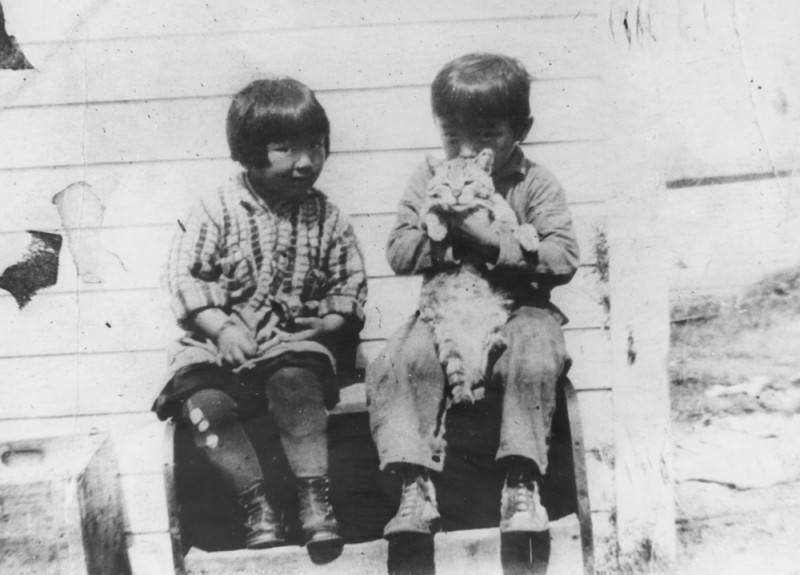 Black and white photo of two Korean American children sitting together. The child on the right holds a cat.