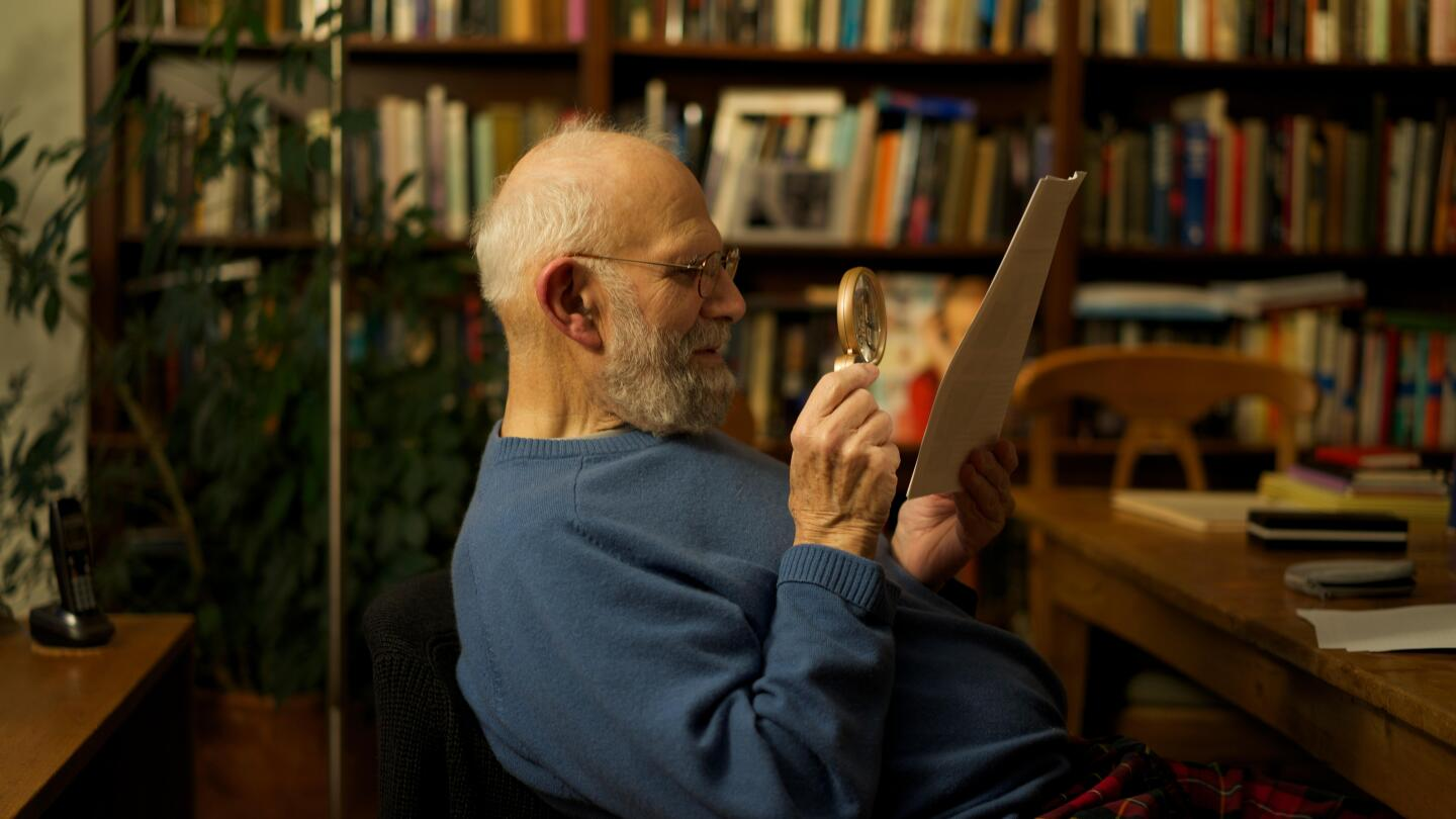Oliver Sacks examines a document in his hand with a magnifying glass.