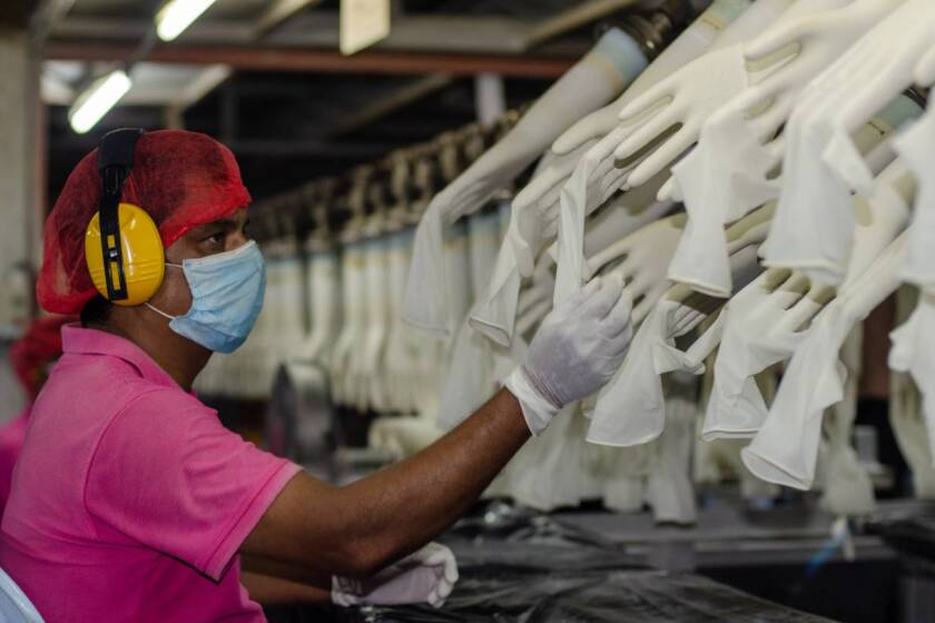 A worker makes checks at the Miditech Gloves' rubber glove factory in Malaysia in 2020. | Miditech Gloves via Thomson Reuters Foundation